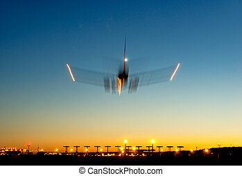 airplane in blurred motion approaching  airport at sunset