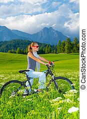 Active woman on bicycle in mountains, beautiful landscape,...