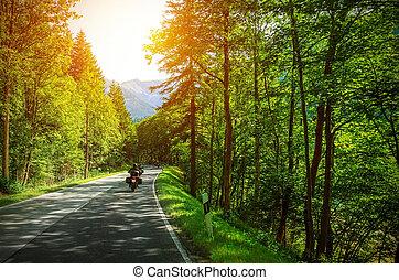 Biker on mountainous road in sunset light, motorcyclist on...