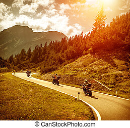Bikers on mountains road in sunset - Group of motorcyclists...