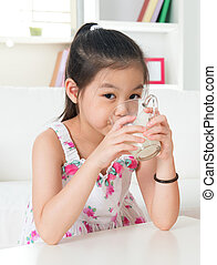 Drinking milk Happy Asian kid drink milk at home Beautiful...