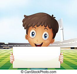 A smiling boy holding an empty signage at the soccer field -...