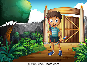 A boy inside the gated yard with a bow and arrow