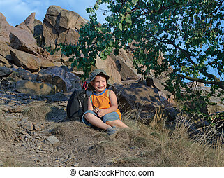 Little boy resting on the mountain in summer - Happy little...