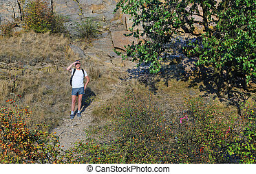 Man out backpacking on a mountain path standing with his...