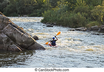 Man rafting with kayak on a fast watercourse - Rear view of...