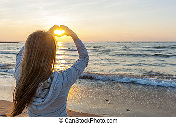 Girl holding hands in heart shape at beach - Blonde young...