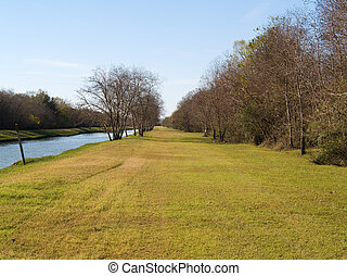 The Green Levee - A levee on the right, with bare trees.