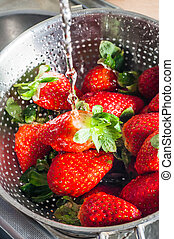Water Washing over Strawberries - A metal sieve resting in a...