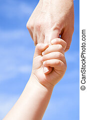 Adult holding a child by the hand