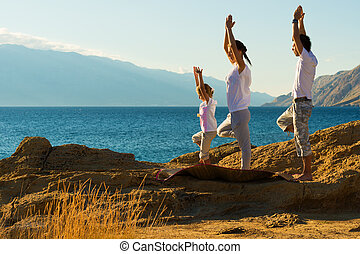 young family doing yoga exercise on the beach