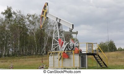 Oil pump working in the forest. Oil industry equipment.