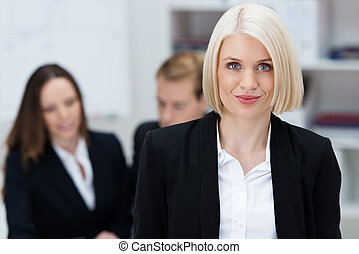 Attractive female business executive standing in front of...