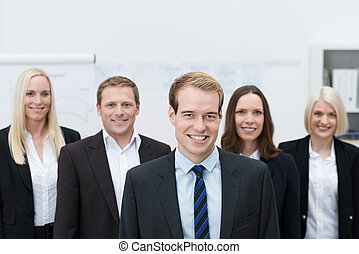 Handsom young manager with a happy team behind him - Handsom...