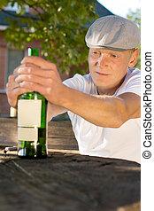 Drunk depressed man holding a bottle of wine - Drunk...