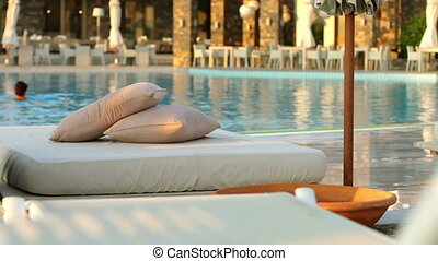 Beach loungers and floating in the pool, the woman