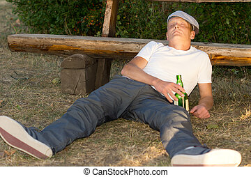 Alcoholic passed out on the ground in a park lying with his...