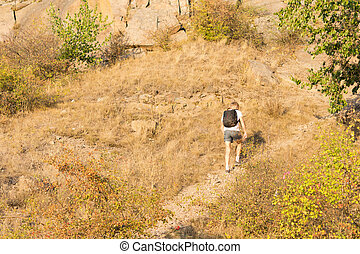 Solitary man hiking on a mountain path - Rear view of a...