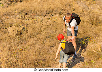 Young boy climbing a mountain with his father being helped...