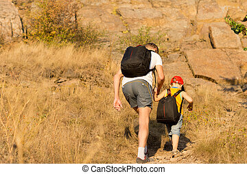 Father and son hiking on a mountain - Father and son wearing...