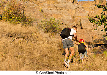 Man helping a young boy hiking on a mountain - Man helping a...