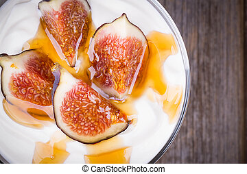 Greek yogurt with figs and honey, in a glass bowl over old...