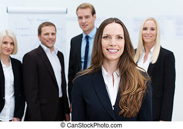 Businesswoman smiling with a team behind her