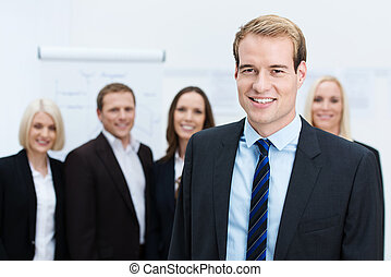 Businessman smiling with a team behind him