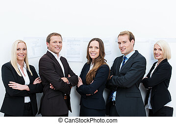Happy professional team standing with folded arms