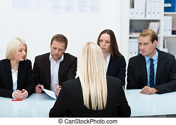 Human resources team conducting an interview reading the...