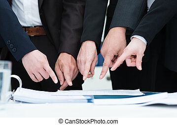 Group of businesspeople pointing to a document on a desk,...