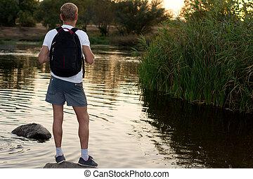 Man standing at a lake at sunset - Man standing overlooking...
