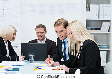 Business men and women in a meeting grouped around a table...