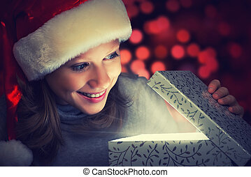 happy woman in a Christmas cap opens the magic box gift