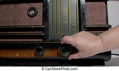 DOLLY: Hand tuning vintage radio - Hand of senior woman...