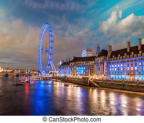 London at night. Thames river with The Eye Panoramic Wheel.