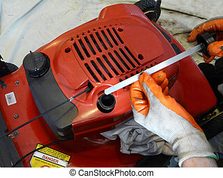Lawn Mower Oil Check - A man wearing nitrile dipped work...