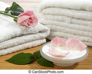 Spa essentials cream, white towel and pink rose