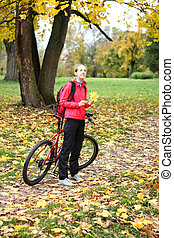 Young girl cyclist with bike enjoy vacation in autumn park