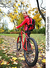Girl cyclist with bike on bicycle walk in autumn park