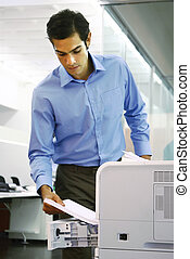 worker using a copy machine - young worker using a copy...