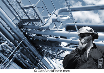 oil and gas worker with large pipelines constructions, blue...