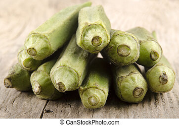 uncooked okra on a wooden background - uncooked organic okra...