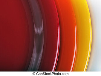 orange, yellow and red colored plates stacked upon each...