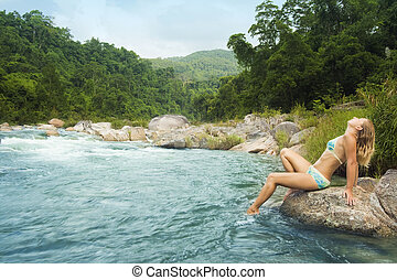 Young woman posing on the stone near jungle river