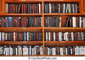 Jewish prayer books on wooden shelves. - Wooden shelves with...