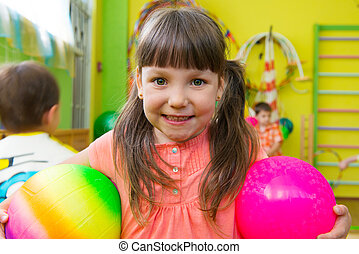 Cute little girl playing at daycare gym with ball