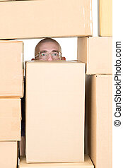 Male face - Man looking through window in pile of cardboard...