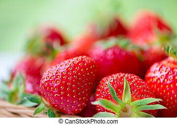 Juicy ripe strawberries in basket against green background