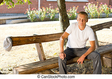 Single man sitting lonely on a wooden bench - Middle-aged...